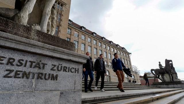 Studierende schreiten die Freitreppe der Universität Zürich hinab, im Vordergrund ein Sockel mit dem Schriftzug der Universität