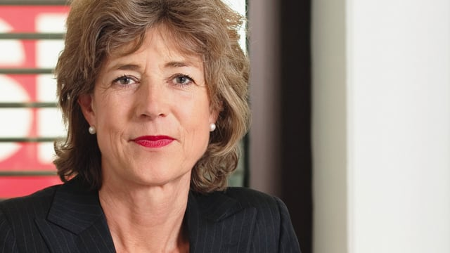 Die Fotografie zeigt ein Porträt von Helen Stehli Pfister, mit halblangen hellbraunen Haaren und rot geschminkten Lippen.