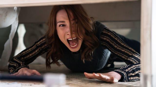 Frau liegt am Boden und schreit.