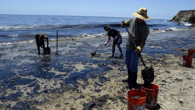Drei Personen schaufeln das Öl am Stran in Plastikkübel.
