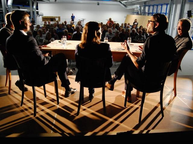 Gruppe am Tisch, Licht- und Schattenspiel am Boden.