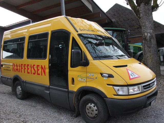 Ein kleiner, gelber Bus mit einer grossen, offenen Seitentüre. Im Hintergrund sieht man noch einen Traktor.