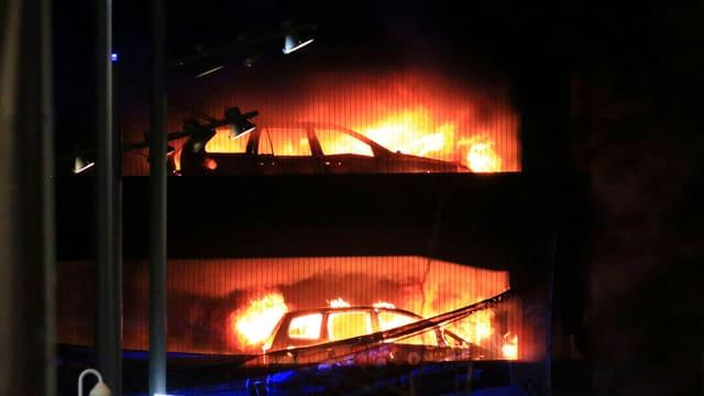 vista sin ina chasa da parcar che arda, duas autos stattan en flommas