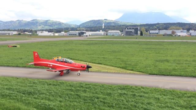 Ein rotes Flugzeug auf der Startbahn.