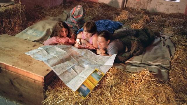 Schlafen im Stroh, drei Jugendliche studieren eine Karte.