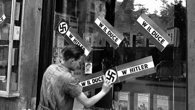 Ein junger Mann klebt Plakate auf das Fenster einer Buchhandlung in Rom, um das Treffen zwischen Mussolini und Hitler in München zu feiern.