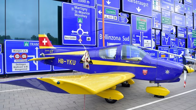Die Fassade des Verkehrshauses Luzern, mit Schildern behangen, ein Flugzeug davor