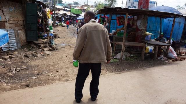 Ein Mann in einem Slum, in der Hand eine Flasche.