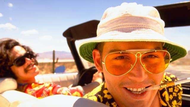 Zwei Männer mit Sonnenbrille Sitzen in einem Cabriolet. Der Beifahrer Blickt in die Kamera, die auf der Rückbank positioniert ist.