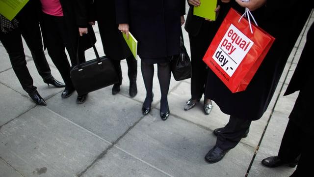 Männer- und Frauenbeine, jemand hält eine Tüte mit der Aufschrift «equal pay day».