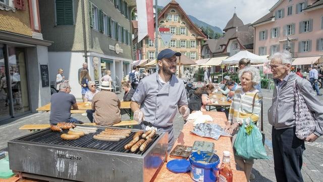 Ein Mann und eine Frau kaufen Würste auf dem Wochenmarkt in Sarnen