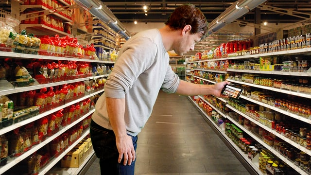 Jürg Tschirren scannt in einem Einkaufszentrum ein Regal mit Produkten.