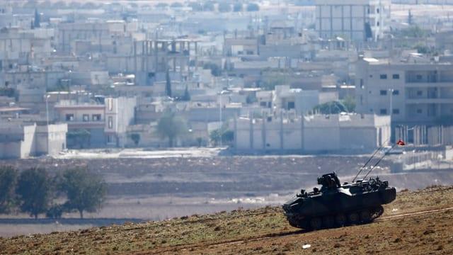 Panzer, im Hintergrund die Stadt Kobane