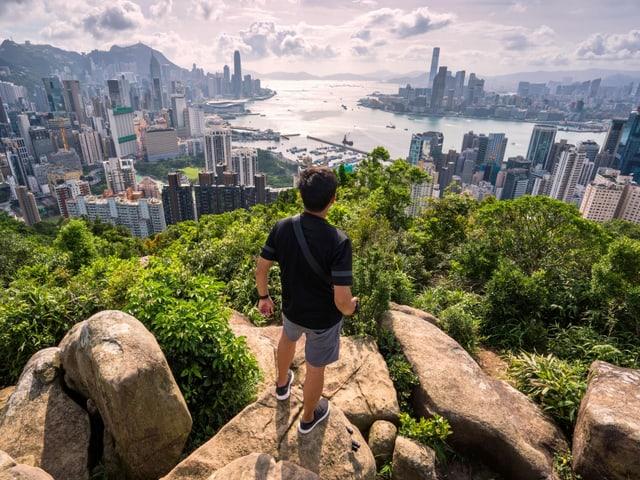 Ein Mann steht auf einem Felsen und schaut auf die Stadt.