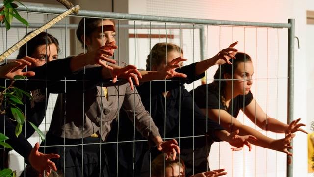 Darstellerinnen strecken ihre Hände durch Gitterstäbe.