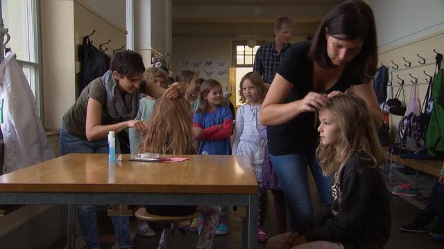 Drei Erwachsene prüfen die Köpfe einer Schulklasse.