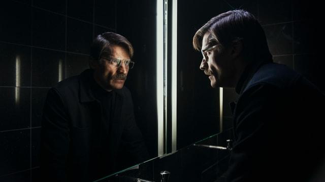 Der hweld des Films steht vor einem Spiegel.