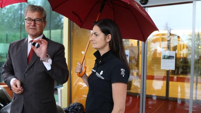 La campiunessa mundiala da curling Binia Feltscher tegn il parasol per il directur da l'hotel.