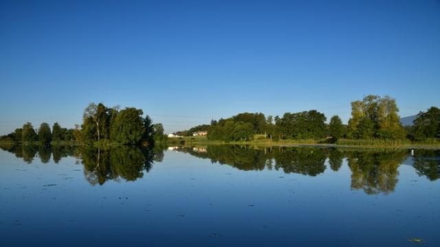 Spiegelglatter See und blauer Himmel.