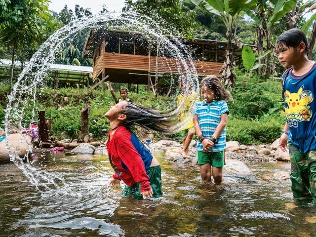 Kinder spielen im Wasser.