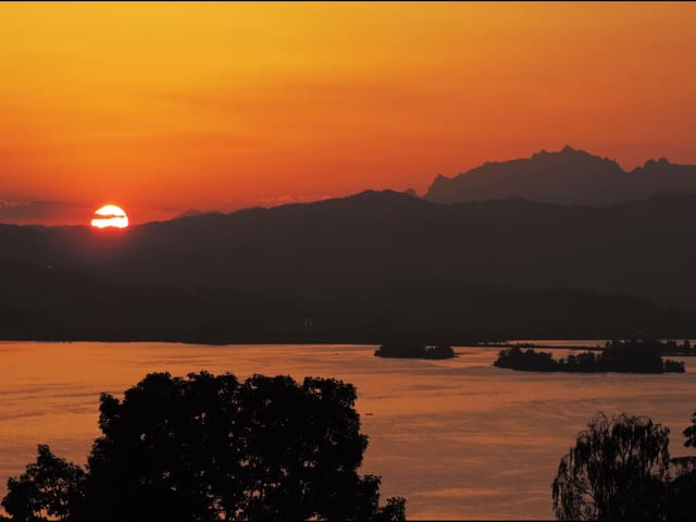 Blick auf den Zürichsee, hinter dem Hügel geht die Sonne auf. Der Himmel ist rot verfärbt.