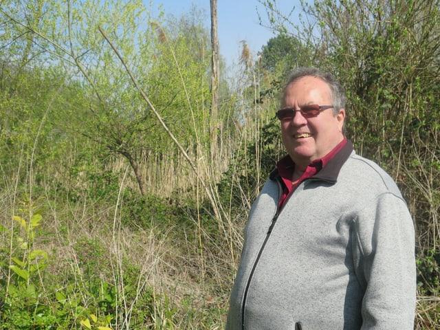 Ein Mann mit einer grauen Jacke vor grünen Pflanzen.