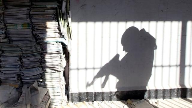Der Schatten eines Rebellen an der Wand, der mit seinem Gewehr hantiert.