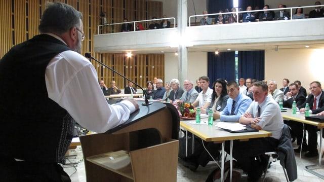 Mann steht am Rednerpult und spricht vor Versammlung.