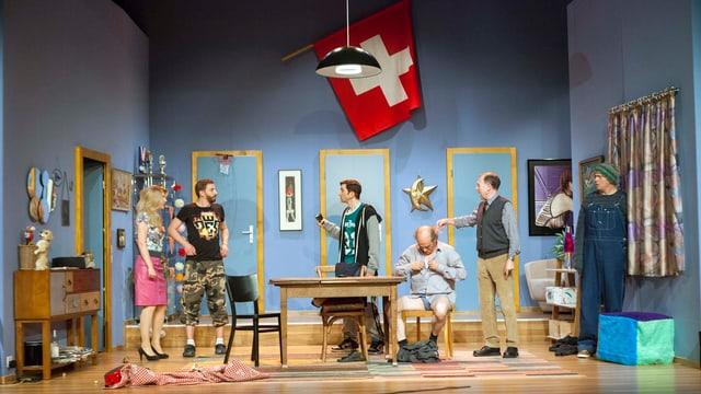 Sechs Schauspieler auf einer Theaterbühne, über ihnen thront die Schweizer Flagge.