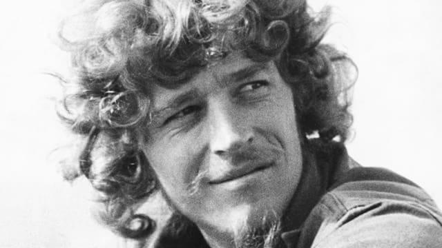 Ein junger Mann mit wildem Lockenkopf lächelt.