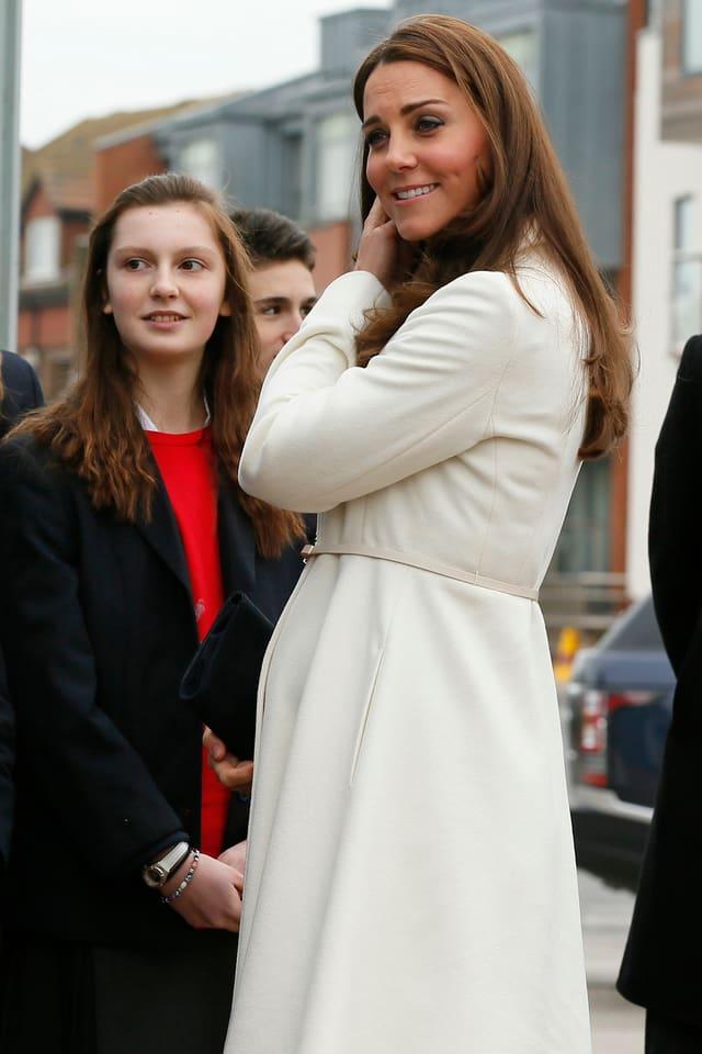 Herzogin Kate in einem weissen Mantel lächelnd und mit Mädchen sprechend.