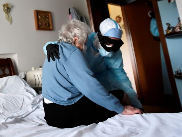 Ein Arzt in Schutzbekleidung besucht eine Seniorin in Bergamo