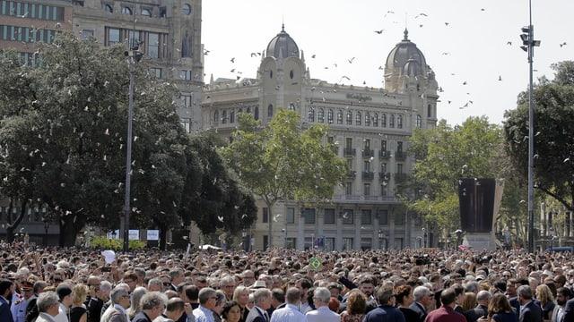 Millis da persunas èn sa rimnadas sin la Placa Catalunya per commemorar las unfrendas cun ina minuta da silenzi.