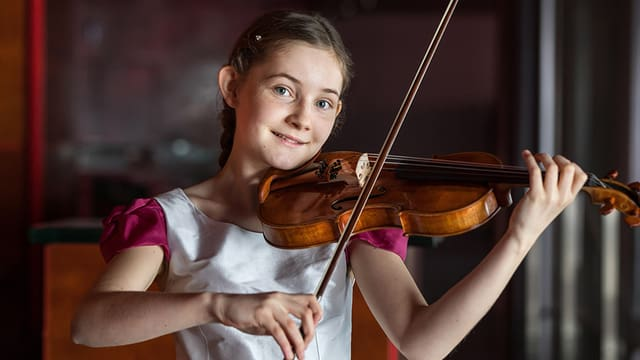 Ein Mädchen im weissen Röckchen spielt Geige und lächelt in die Kamera.
