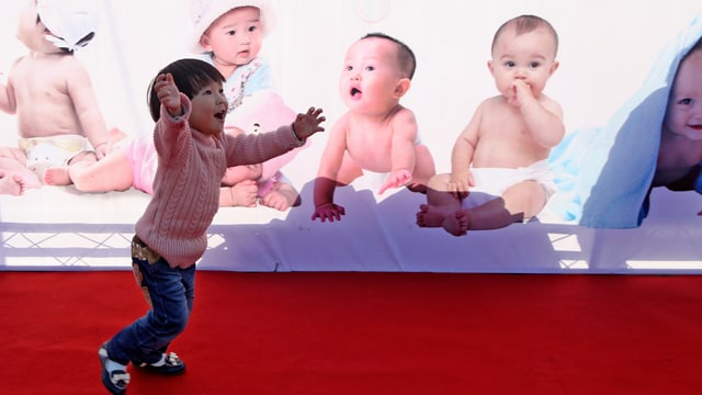 Ein chinesisches Kind vor einer Bilderwand mit Babys