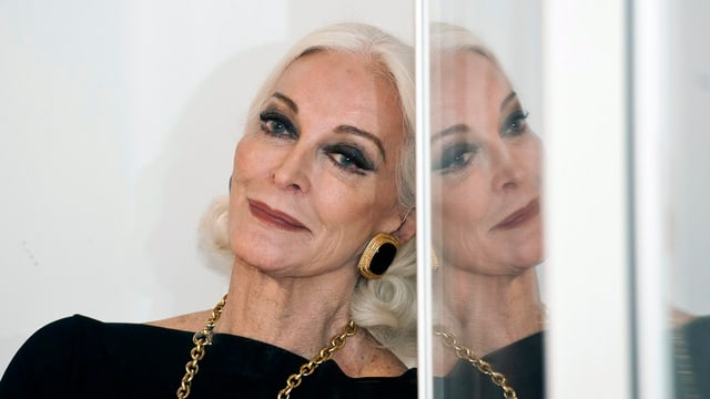 Carmen Dell'Orefice blickt entspannt in die Kamera. Um den Hals trägt sie eine goldene Kette.