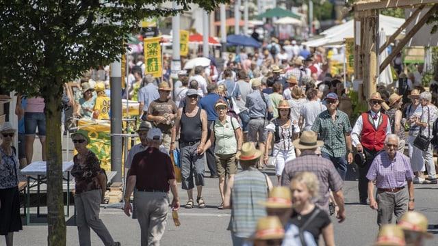 Menschen gehen durch eine Strasse.