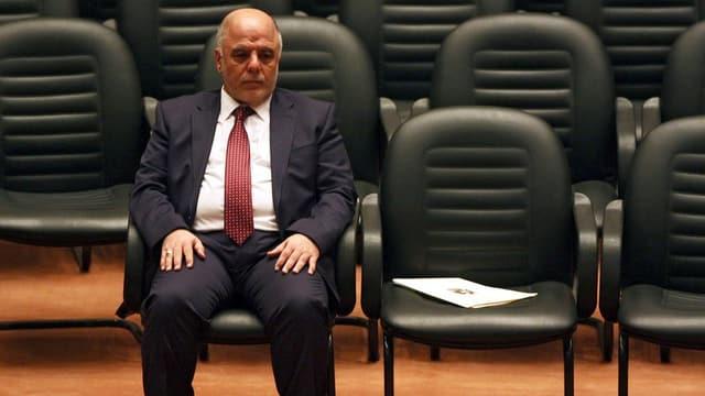 Ein Mann sitzt auf einem Stuhl.