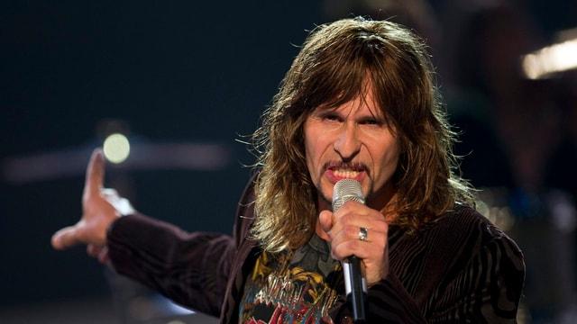 Steve Lee singt und hält ein Mikrofon in der Hand.