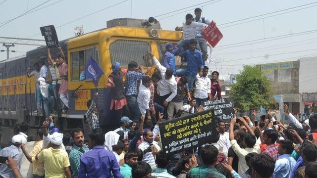 Wütende Männer mit Transparenten klettern auf eine Lokomotive.