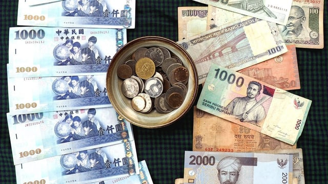 Diverse asiatische Banknoten und eine Schale mit Kleingeld.