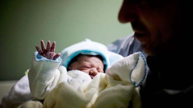 Ein Mann hält ein frischgeborenes Kind im Arm.