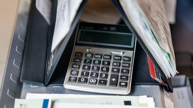 Taschenrechner zwischen Ordnern