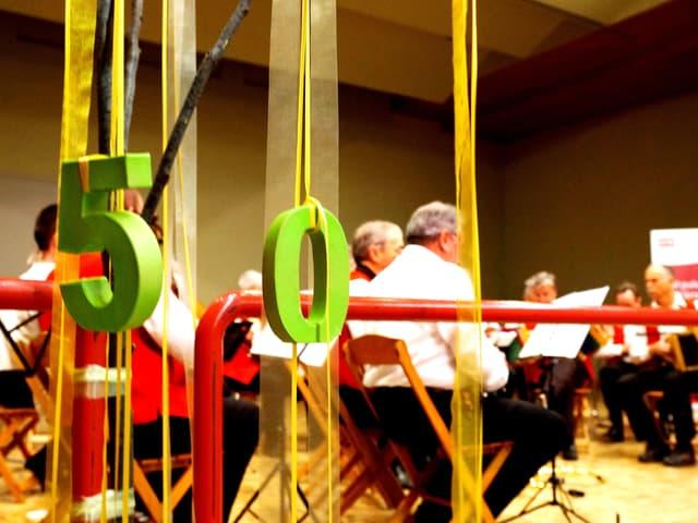 Blick von Hinten auf Musiker. Davor zu sehen eine Zahl 50 aus Dekozahlen.