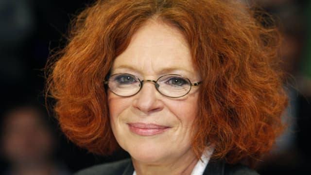 Eine Frau mit roten Locken (auf Kinnhöhe geschnitten), Brille und dunkel geschminkte Augen.