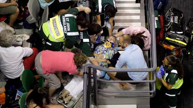 Eine ältere Dame wird nach ihrem Sturz von Sanitätern behandelt.