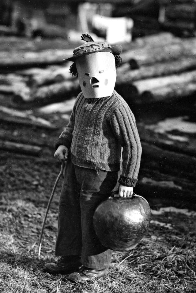 Schwarz-Weiss-Bild: Ein Knabe mit einer Makse auf dem Kopf und einer Glocke in der Hand.