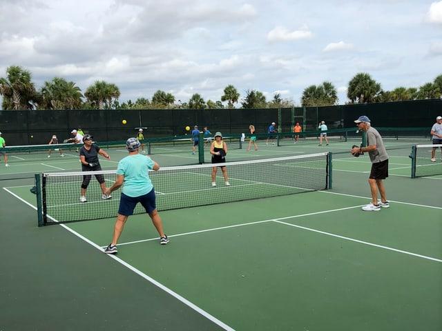 Gemischtes Doppel auf einem kleinen grünen Tennisplatz