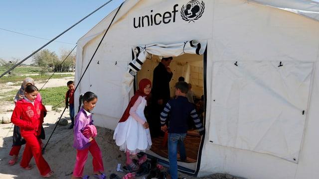Kinder betreten ein UNICEF-Zelt.