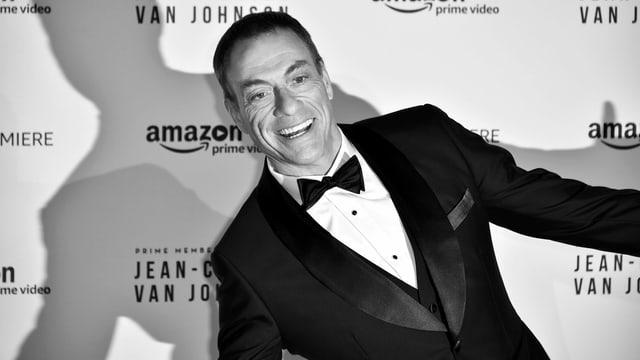 Schwarz-Weiss-Bild von Jean-Claude Van Damme vor einem Plakat.